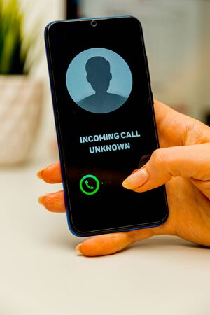 Unknown caller. A man holds a phone in his hand and thinks to end the call. Incoming from an unknown number. Incognito
