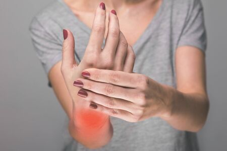 Elderly woman suffering from pain, weakness and tingling in wrist. Causes of hurt include osteoarthritis, rheumatoid arthritis, gout or wrist sprain. Health care Imagens