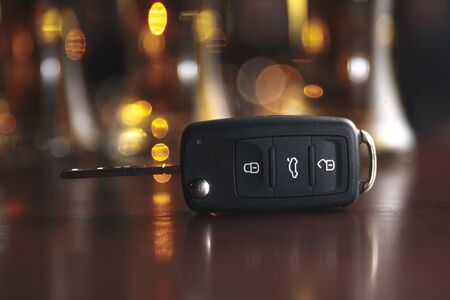 Drinking and driving concept. Car key on a wooden table, pub