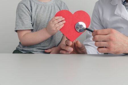 Man and kid are listening to the heart by stethoscope. Support your health concept.