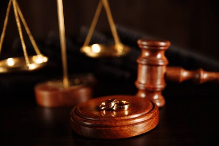 Wooden hammer of the judge. Judge hammer and rings on the wooden table. Divorce divorce proceedings