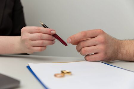 Prenuptial agreement concept. Man and woman signing notary document together.