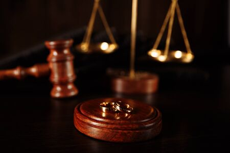 Wedding rings on the stand from a tree, hammer of a judge on a wooden background. Divorce divorce proceedings