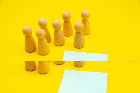 Teamwork, teambuilding mockup, company structure. Wooden figures stands over isolated yellow background near blue sticky note, place for text.