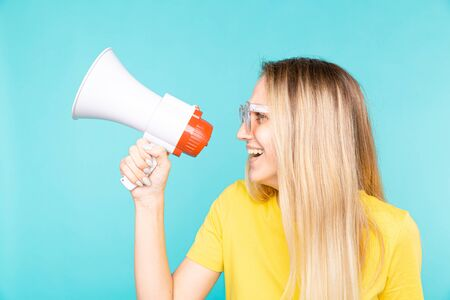 Young woman in yellow t-shirt over blue wall shouting through a megaphone and smilling