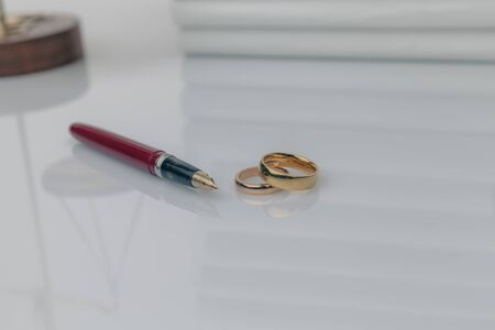 Divorce concept. Golden rings on the table with wooden hammer and money.