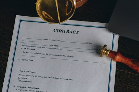 Top view of contract in clipboard lying at office on wooden table with laptop and documents