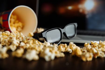 Popcorn and 3d glasses in front of laptop playing movie. Film, fastfood. Entertainment concept