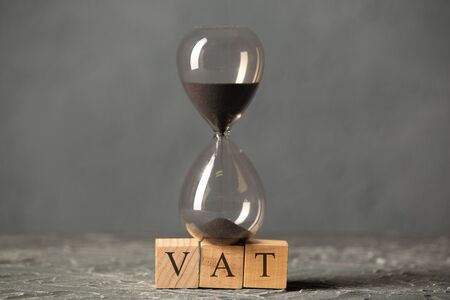 Hourglass or sandglass on cube wooden block with alphabets VAT, Value Added Tax on the table. Stock Photo