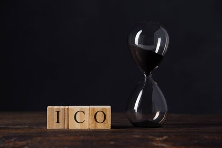 ICO, Initial Coin Offering for crypto currency to buy and sell on public concept, hourglass on wooden cube blocks with the word ICO on wood table, dark black background. Stock Photo