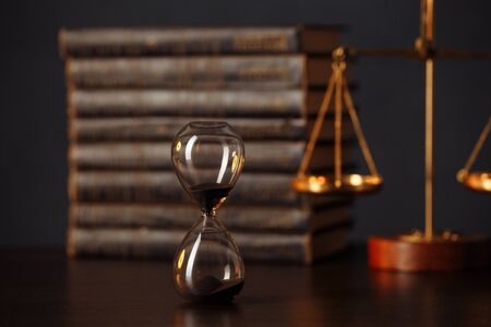 Judges gavel, scales of justice, books and hourglass on wooden table. Law concept Foto de archivo