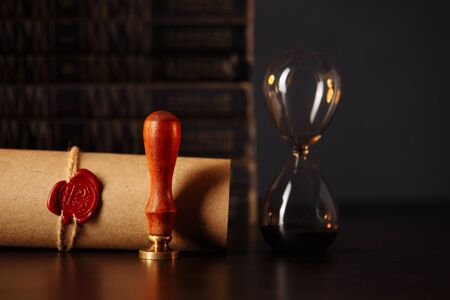 Wooden gavel, hourglass and stamp on testament and last will on wooden table. Notary public tools close-up Foto de archivo