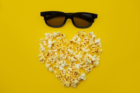 Love Cinema concept of popcorn arranged in a heart shape and glasses on yellow background Banco de Imagens