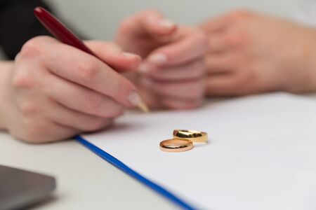 Divorce in process. Woman and man signing document. Wedding rings on the table. Banque d'images