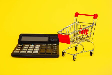 Clever shopping and save money concept. Shopping cart and calculator on yellow background.