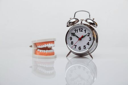 White paper tooth with alarm clock on blue background. Time to dental health. Dentist day concept. Flat lay, top view, copy space for text