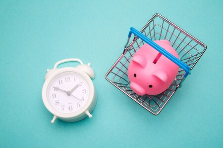 Shopping time concept. Piggy bank and supermarket trolley with alarm clock on blue background. Overhead view.