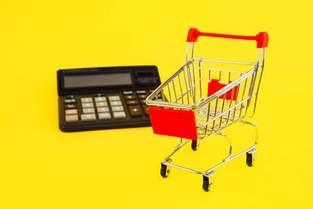 Clever shopping and save money concept. Shopping cart and calculator on yellow background