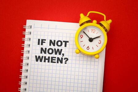 If Not Now When, text on a notebook with yellow alarm aside on red background. Motivating and inspiring question Stock Photo