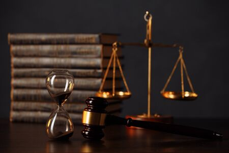 Judge's gavel, books, scales of justice and hourglass on wooden table. Law and justice concept.