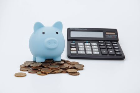Blue piggy or coin bank or piggybank or money box on coins and calculator - finance and savings concept on white background