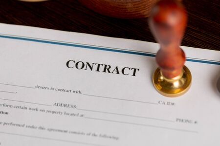Top view of contract in clipboard lying at office on wooden table with laptop and documents Stock Photo