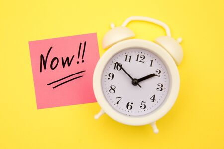 Sticker with handwriting the word NOW on alarm clock on yellow background with copy space using as stop procrastination, self discipline or motivation to complete task Stok Fotoğraf