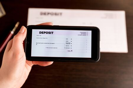 Man Taking Photo Of Cheque To Make Remote Deposit In bank. Stockfoto