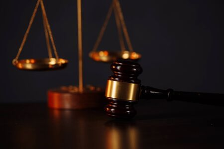 Gavel and scales on wooden table. Punishment concept