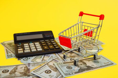 Shopping cart, money and calculator, concept for grocery expenses and consumerism.