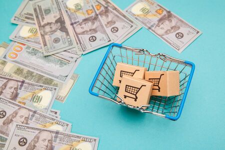 Money banknotes dollar and shopping basket with boxes on blue background.Easy shopping with finger tips for consumers.Online shopping and delivery service.
