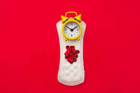 Menstruation woman hygiene concept. Minimal flat lay menstrual pad and yellow alarm clock on a red background