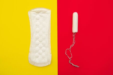 Women intimate hygiene products - sanitary pad and tampon on colorful background