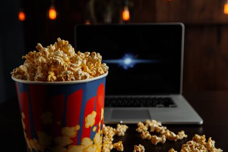 Have a good evening watching a movie on a laptop with popcorn. Entetainement concept.