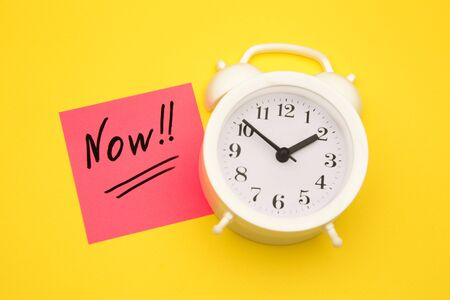 Sticker with handwriting the word NOW on alarm clock on yellow background with copy space using as stop procrastination, self discipline or motivation to complete task. Stok Fotoğraf