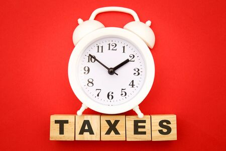 Time to pay TAX concept. Wooden cubes and alarm clock on red background.