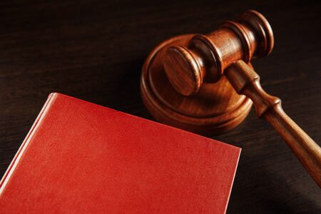 Dark red book and wooden gavel on it. Lawyer library concept.
