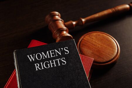 Womans rights book at the desk. Protecting female concept.