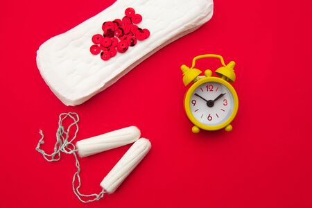 Sanitary pads and tampons, alarm clock on red background. Females menstrual cycle concept