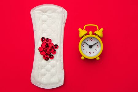 Medical conception photo. Daily pad and yellow clock on red background. Woman critical days, gynecological menstruation cycle. Menstruation sanitary woman hygiene