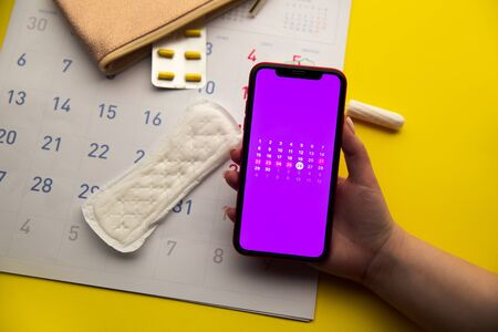 Menstrual cycle concept. Calendar for the month with marks and a mobile application on the smartphone screen. Contraceptive and sanitary pads on the background.