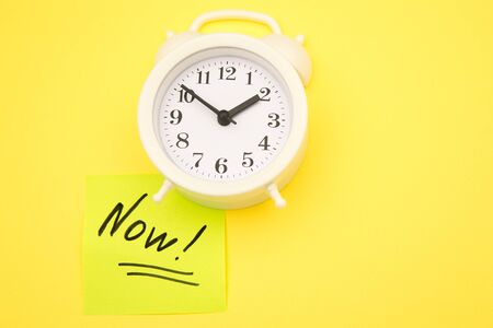 Sticker with handwriting the word NOW on alarm clock on yellow background with copy space using as stop procrastination, self discipline or motivation to complete task. Foto de archivo