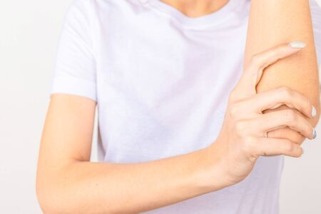 Woman suffering from chronic joint rheumatism. Elbow pain and treatment concept.