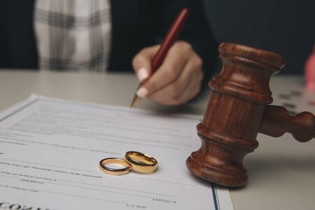 Hands of wife, husband signing decree of divorce, dissolution, canceling marriage, legal separation documents, filing divorce papers or premarital agreement prepared by lawyer. Wedding ring Standard-Bild