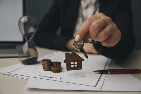 Close up wooden toy house with Woman signs a purchase contract or mortgage for a home, Real estate concept. Reklamní fotografie
