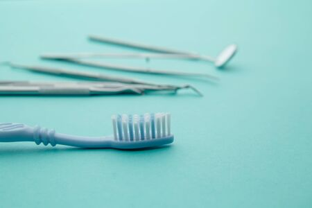 Dentist tools,mirror, spatula, tweezers and toothbrush on a blue background Stockfoto