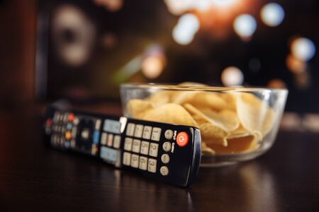 Snacks and Tv remote control at the table