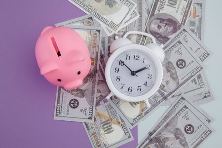Alarm clock on dollars banknotes and piggy bank on colorful background. Time to invest. Foto de archivo - 150556991