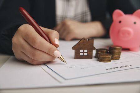 Close up wooden toy house with Woman signs a purchase contract or mortgage for a home, Real estate concept. Stock Photo