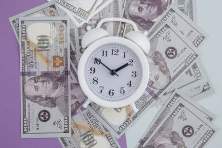 Alarm clock on dollars banknotes on colorful background. Time is money concept Banque d'images